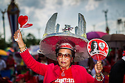 10 MAY 2014 - BANGKOK, THAILAND:  A Red Shirt with a model of Democracy Monument, a Bangkok landmark, on her head. Thousands of Thai Red Shirts, members of the United Front for Democracy Against Dictatorship (UDD), members of the ruling Pheu Thai party and supporters of the government of ousted Prime Minister Yingluck Shinawatra are rallying on Aksa Road in the Bangkok suburbs. The government was ousted by a court ruling earlier in the week that deposed Yingluck because the judges said she acted unconstitutionally in a personnel matter early in her administration. Thailand now has no functioning government. Red Shirt leaders said at the rally Saturday that any attempt to impose an unelected government on Thailand could spark a civil war. This is the third consecutive popularly elected UDD supported government ousted by the courts in less than 10 years.   PHOTO BY JACK KURTZ