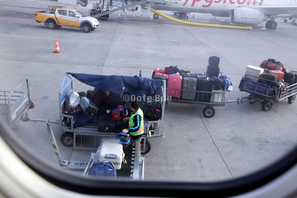 airport luggage handler loading seen from within the airplane
