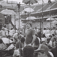 """1. When was this photo taken?<br /> <br /> June 16, 1991<br /> <br /> 2. Where was this photo taken?<br /> <br /> Giants Stadium, East Rutherford, NJ<br /> <br /> 3. Who took this photo?<br /> <br /> I did.<br /> <br /> 4. What are we looking at here?<br /> <br /> My former Boston University college roommate Mike Mokrzycki standing in the """"tapers"""" section on the field at Giants Stadium before the beginning of a Grateful Dead concert in June 1991.<br /> <br /> 5. How does this old photo make you feel?<br /> <br /> Makes me feel about my present age (55).<br /> <br /> 6. Is this what you expected to see?<br /> <br /> Not at all. I vaguely remember going to this concert (I went to a lot of concerts over the years and a lot of Grateful Dead concerts), but I did not remember taking any photos and was very surprised when I saw the images on this lost roll.<br /> <br /> 7. What kind of memories does this photo bring back?<br /> <br /> This brings back a lot of very good memories. Mike was one of my best college friends and he died unexpectedly - way too young - in December 2014.<br /> <br /> 8. How do you think others will respond to this photo?<br /> <br /> I think it's an unusual scene - you don't typically see microphones on stands with umbrellas at concerts, or anywhere for that matter. Anyone who knew Mike will smile seeing him in his element. I also think this photo captures a small part of the experience of going to a Grateful Dead concert, especially for those fans who were into taping the shows."""