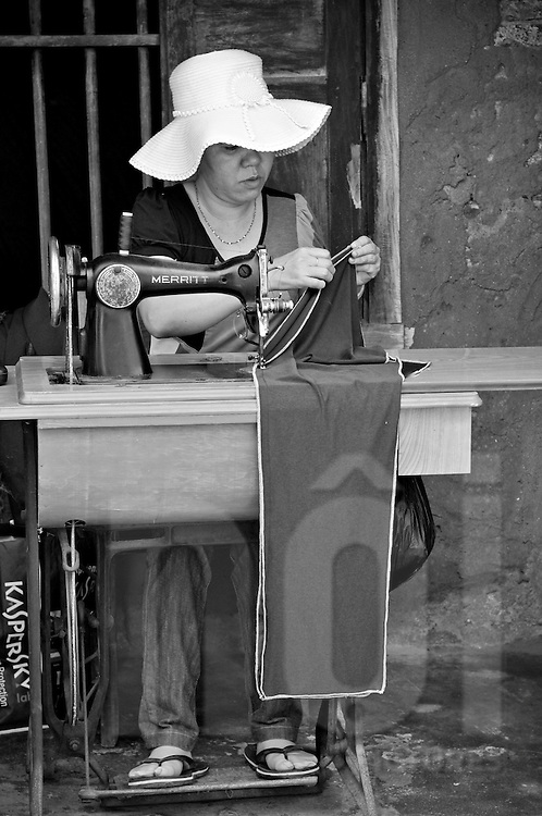 Vietnamese woman sewing in the street. The sewing machine is a very old model operated with feet.  Khanh Hoa area, Vietnam, Asia