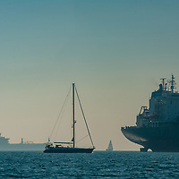Sailboats pass container ships anchored in San Francisco Bay, waiting to load cargo at docks in either Oakland or San Francisco.