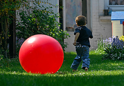 BRUSSELS, BELGIUM - APRIL-25-2007 - A child plays with a big red ball. (PHOTO © JOCK FISTICK)