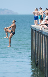© Licensed to London News Pictures 22/07/2021. Whitstable, UK. A man having fun jumping off the Harbour Arm in Whitstable. Another hot heatwave day as people enjoy a day out at Whitstable in Kent. Photo credit:Grant Falvey/LNP