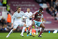Alex Song of West Ham United holding the ball from Gylfi Sigurdsson of Swansea City. Barclays Premier league match, West Ham Utd v Swansea city at the Boleyn ground, Upton Park in London on Sunday 7th December 2014.<br /> pic by John Patrick Fletcher, Andrew Orchard sports photography.
