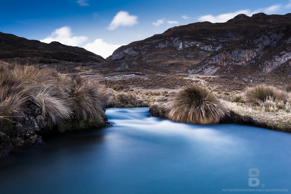 A long exposure as the river and sky match blue and white hues in a soft and sureal landscape in the the Cordillera Huayhuash of the Andes Mountains in Peru.