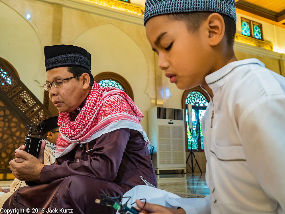 06 JULY 2016 - BANGKOK, THAILAND:  A muezzin and his son perform the call to prayer before Eid services at Ton Son Mosque in the Thonburi section of Bangkok. Eid al-Fitr is also called Feast of Breaking the Fast, the Sugar Feast, Bayram (Bajram), the Sweet Festival or Hari Raya Puasa and the Lesser Eid. It is an important Muslim religious holiday that marks the end of Ramadan, the Islamic holy month of fasting. Muslims are not allowed to fast on Eid. The holiday celebrates the conclusion of the 29 or 30 days of dawn-to-sunset fasting Muslims do during the month of Ramadan. Islam is the second largest religion in Thailand. Government sources say about 5% of Thais are Muslim, many in the Muslim community say the number is closer to 10%.       PHOTO BY JACK KURTZ