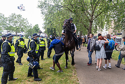 Licensed to London News Pictures. 17/06/2021. London, UK. A man gets knocked by a horse as police and bailiffs clear an anti-lockdown camp on Shepherd's Bush Green this morning. The demonstrators who have been camping on the green since 31 May 2021 were forced out of their tents this morning with many of their possessions left behind as police in riot gear and on horseback forced everyone out of the west London green space. The protesters have been demonstrating against lockdown, mask wearing, vaccines and testing. Photo credit: Alex Lentati/LNP