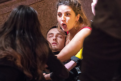 """© Licensed to London News Pictures . 16/12/2017. Manchester, UK. A man, understood to be injured, is tended to by a woman , on Peter Street . Revellers out in Manchester City Centre overnight during """" Mad Friday """" , named for historically being one of the busiest nights of the year for the emergency services in the UK . Photo credit: Joel Goodman/LNP"""