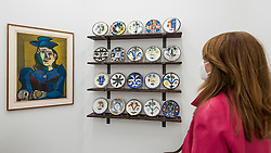 "© Licensed to London News Pictures. 01/09/2020. LONDON, UK. A woman poses with (L to R) ""Femme assise (Dora Maar) [Seated Woman (Dora Maar)]"", 1955, and ""The Complete Set of 20 »Visage« plates"", 1963, all by Pablo Picasso.  Preview of ""Atelier Picasso"", a new exhibition recreating Pablo Picasso's studio in Cannes featuring his drawings, prints, ceramics and furniture.  The show is at Bastian gallery in Mayfair 3 September to 31 October 2020.  Visitors will be required to wear a facemask and practice social distancing.  Photo credit: Stephen Chung/LNP"