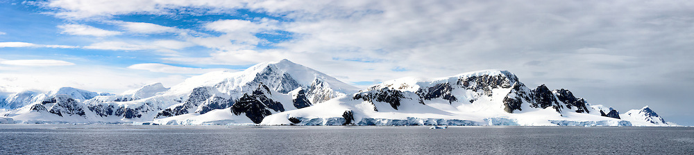A high resolution panorama of snow and ice-covered mountains along the Gerlache Strait on the western coast of the Antarctic Peninsula.