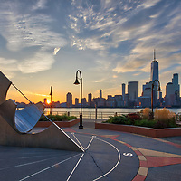 Jersey City with the famous sun dial and New York City skyline photographed on a quiet morning at sunrise. <br />