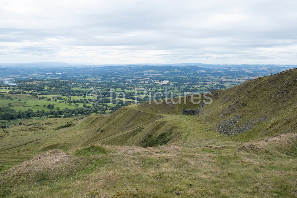 Old quarry on top of Titterstone Clee Hill on 22nd July 2020 in Cleedownton, United Kingdom. Titterstone Clee Hill, sometimes referred to as Titterstone Clee or, incorrectly, Clee Hill, is a prominent hill in the rural English county of Shropshire, rising at the summit to 533 metres above sea level. It is one of the Clee Hills, in the Shropshire Hills Area of Outstanding Natural Beauty. Most of the summit of the hill is affected by man-made activity, the result of hill fort construction during the Bronze and Iron Ages and, more recently, by years of mining for coal and quarrying for dolerite, known locally as dhustone, for use in road-building. Many derelict quarry buildings scattered over the hill are of industrial archaeological interest as very early examples of the use of reinforced concrete. Several radar domes and towers operate on the summit of the hill. The largest of the radar arrays is part of the National Air Traffic Services NATS radar network, and covers one of 30 overlapping regions of UK airspace. The one on Titterstone Clee monitors all aircraft within a 100-mile radius.