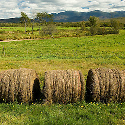 Hay bales and the South Branch of the Israel River as it runs through the E and R Dairy Farm in Jefferson, New Hampshire.