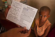 A Tuberculosis treatment record card for a 6 year old Indian girl in a health clinic in Tehkhand Slum, Delhi, India.  The young child will receive at least 6-months treatment course of combination antibiotics that must been taken everyday, otherwise fatal drug resistance can develop.  The medication is free and provided by the government. TB is an infectious disease and a huge public health issue often associated with poverty.  TB is completely curable, however TB rates are increasing and India suffers from the highest burden of TB in the world with many pediatric cases.