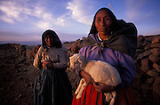 A shepherdess of Amantani Island cradles a lamb in her arms as the sun sets over Lake Titicaca.