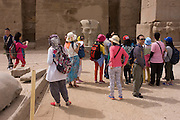 Tourist groups stand and photograph beneath the giant colossi in the Court of Ramesses II, at the ancient Egyptian Luxor Temple, Nile Valley, Egypt. The temple was built by Amenhotep III, completed by Tutankhamun then added to by Rameses II. Towards the rear is a granite shrine dedicated to Alexander the Great  and in another part, was a Roman encampment. The temple has been in almost continuous use as a place of worship right up to the present day.