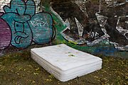 An abandoned mattress on the ground among Autumn leaves on the Regent's Canal in Hackney, on 16th October 2018, in London, England.