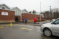 "Principal Tara Beauchemin coordinates handing out packets for K-4 students and laptops for 5th grade students during the drive-thru ""pick up"" at Elm Street School Friday.   (Karen Bobotas/for the Laconia Daily Sun)"