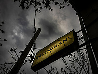 A yellow RESTAURANT sign and menacing looking weather.