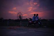Young Vietnamese couple sit on their motorbike gazing at the sunset over Hanoi, Vietnam, Southeast Asia