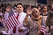 04 JULY 2012 - PHOENIX, AZ:  ISRAEL NEVAREZ (left), originally from Mexico, and MAI ALI, originally from Somalia, take the oath of citizenship Wednesday. About 250 people, from 62 countries, were naturalized as US citizens during the 24th Annual Fiesta of Independence naturization ceremony at South Mountain Community College in Phoenix Wednesday. The ceremony was presided over by the Honorable Roslyn O. Silver, Chief United States District Court Judge.   PHOTO BY JACK KURTZ