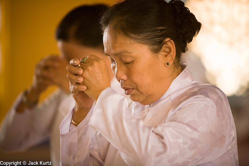 """10 MARCH 2006 - TAY NINH, VIETNAM: Women pray at the Cao Dai temple in Tay Ninh. The Cao Dai complex in Tay Ninh is the sect's headquarters. The Cao Dai religion is a blending of Buddhism, Confucianism, Taoism, Christianity and Islam. There """"saints""""  include Chinese leader Sun Yat Sen and French author Victor Hugo. There are about two million members of the Cao Dai religion in Vietnam. British author Graham Greene, who wrote about the Cao Dai in the """"The Quiet American"""" said the relegion was """"a Walt Disney fantasia of the East."""" Photo by Jack Kurtz / ZUMA Press"""