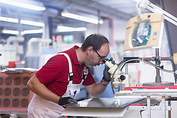 Male engineer examining circuit board in industry, Hanover, Lower Saxony, Germany