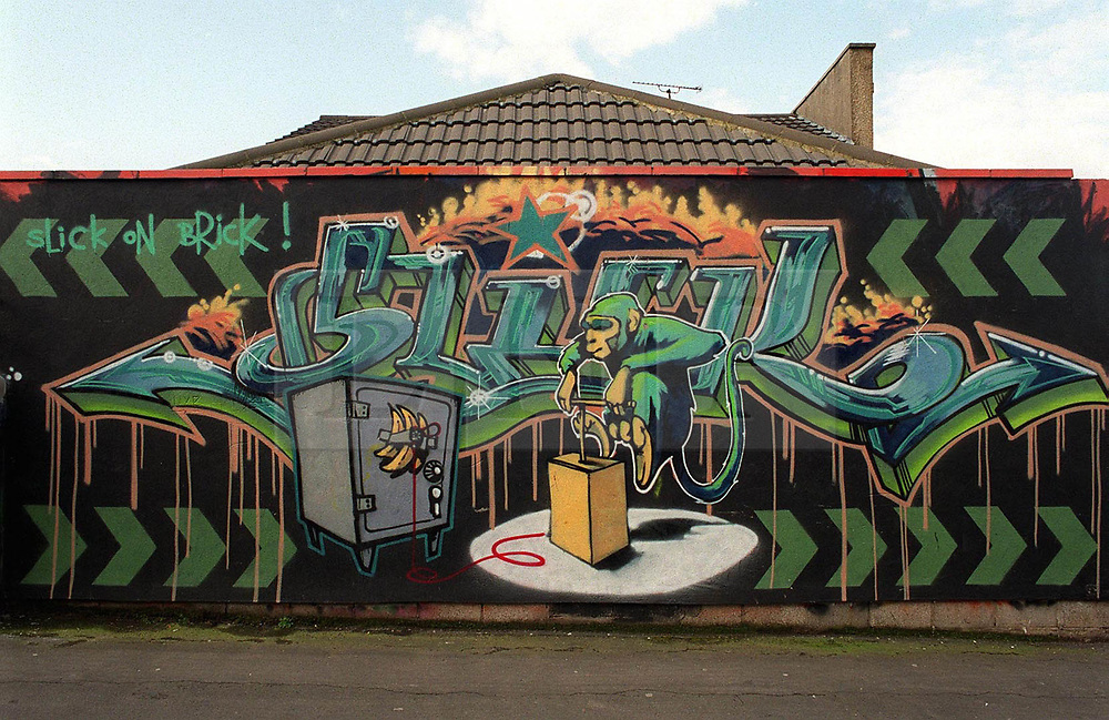 """© Licensed to London News Pictures.  02/11/2017; Bristol, UK. FILE PICTURE dated early 2000. """"Slick on Brick"""", an early work by graffiti artist Banksy showing a monkey with a detonator blowing up a safe, painted on a garage wall of a house in Easton Bristol which is being auctioned this evening, 02/11/2017. The existence of the Banksy work may affect the bidding for the house beyond the guide price of £250,000 to £300,000, some experts suggest the sale could fetch far more, up to £1million. The piece was painted before Banksy's first formal show of work at the Severnshed restaurant from 29 February to 02 April 2000. The work was subsequently painted over and the owner of the house commissioned a new mural by artist 3rdEye. It is not known how much of the original Banksy piece is underneath the subsequent layers of paint or whether it can be restored. Picture credit : Simon Chapman/LNP"""