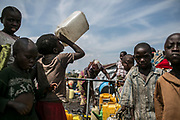 A boy drinks water as other children and woman fetch water from the water stand inside Mugunga III IDP camp.