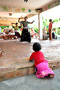 Young girl (2 years old) watching older children at traditional Balinese dance school. Sanur, Bali, Indonesia.
