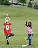 Third-graders Veronica Langham, left, and Jada Reed from Anna S. Kuhl Elementary School in Port Jervis do yoga in the festival field during a visit to Bethel Woods Center for the Arts on Thursday, June 6, 2013. The monument for the 1969 Woodstock Festival is in the background.