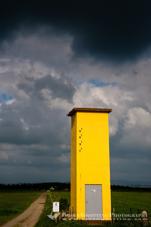 Norway, Revtangen. A yellow transformer house below a dark sky.