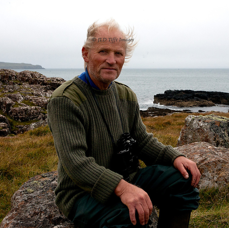 Builder, bird watcher, fisherman, seated on a boulder at Kildowie, Isle of Mull, Scotland.  Tom can make or fix just about anything.