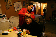 """Tia heads to the back bedroom as her grandmother, Aggie Davis, gets her hair done by Tia's aunt, Beverly Davis. """"My grandmother is the glue that holds our family together. If someone has a problem it will get worked out during Sunday dinner at grandma's,"""" said Tia."""