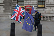 As the EUs Chief negotiator Michel Barnier meets Theresa May in London to discuss the next stage of Brexit, anti-Brexit protesters walk with the Union Jack and EU flag past a telephone kiosk in Whitehall,  near Downing Street, the official residence of the Prime Minister, on 5th February 2018, in London England.