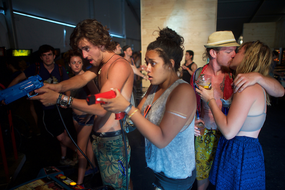 T. J. Chase, 33, and Stephanie Dandaraw, 21, kiss in an arcade while others play video games during the Firefly Music Festival in Dover, Delaware June 20, 2015.  According to organizers, attendance exceeded 90,000 for the four day festival, which featured more than 110 acts, and was set in 105 acre grounds of the Dover International Speedway.