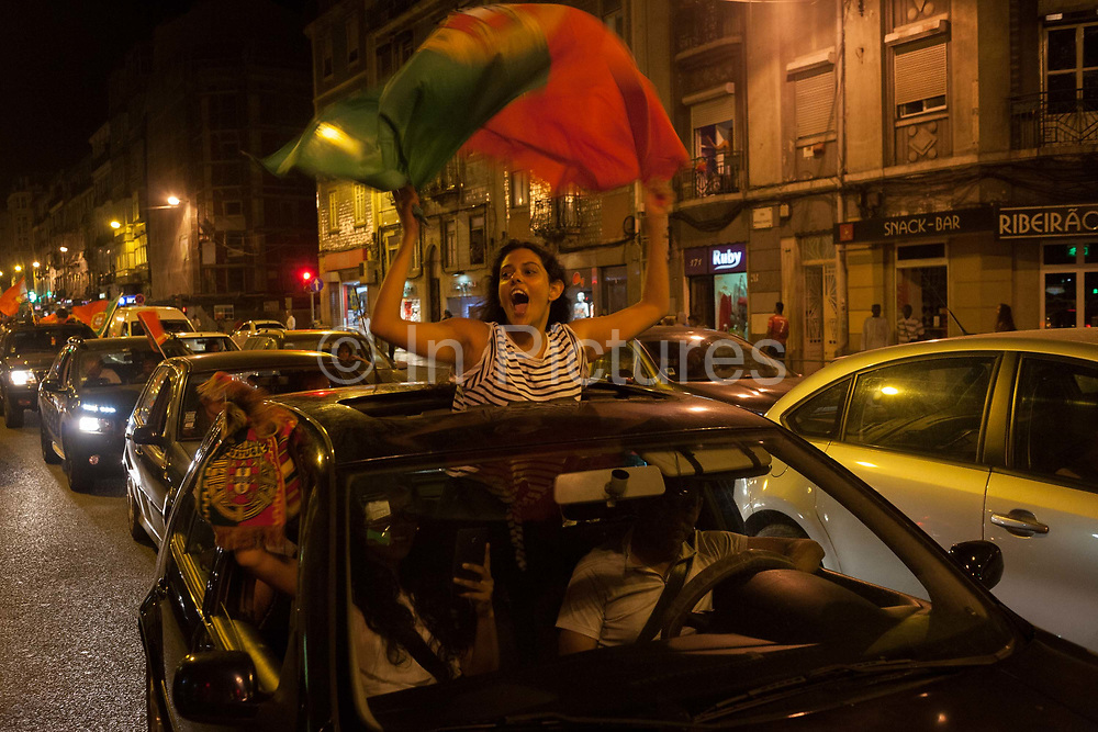 A girl Portuguese football fan celebrates her countrys victory over France in the Euro 2016 tournament final on 10th July 2016, in Lisbon, Portugal. Waving their national flag above their heads, they wave to passers-by after the final whistle in the game that captivated Portugal with their hero, Christiano Ronaldo the symbol of their well-being and patriotism.