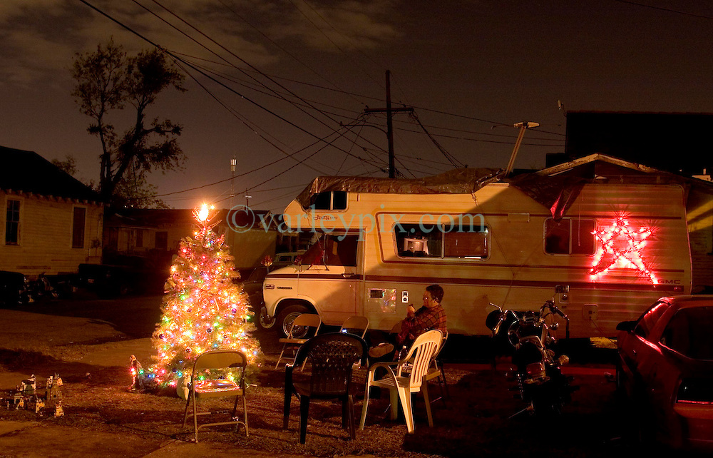 21 December 05. New Orleans, Louisiana. Post Katrina aftermath.<br /> A camper van, the new home of Pijer Day sits outside what was once her home in the flood ravaged Mid City neighbourhood. Pijer erected a tree with a miniature village on the corner of the street to cheer the four residents who have returned to the neighbourhood. All lights powered by generator.<br /> Photo; ©Charlie Varley/varleypix.com