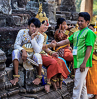 Painfully Bored: A group of traditionally dressed Cambodian dancers rest and amusing themselves in the shade of ancient ruins, the exception; a young man who looks to be both terribly bored and dejected, Bayon of Angkor Thom, Siem Reap Cambodia.