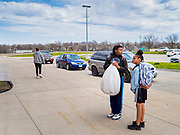 22 APRIL 2020 - DES MOINES, IOWA: Students wait for their grab and go school lunch at Edmunds Elementary School. Schools in Iowa are closed for the rest of the school year because of the COVID-19 (Coronavirus/SAR-CoV-2) pandemic. Des Moines Public Schools expanded their school lunch and distance learning efforts this week. Lunches are being distributed at all of the district's elementary and middle schools and officials have started distributing computers so students can participate in distance learning. The meal distribution was done according to social distancing guidelines.          PHOTO BY JACK KURTZ