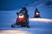 UNIS students practice driving snowmobiles through Adventdalen, Svalbard as part of their basic safety training.