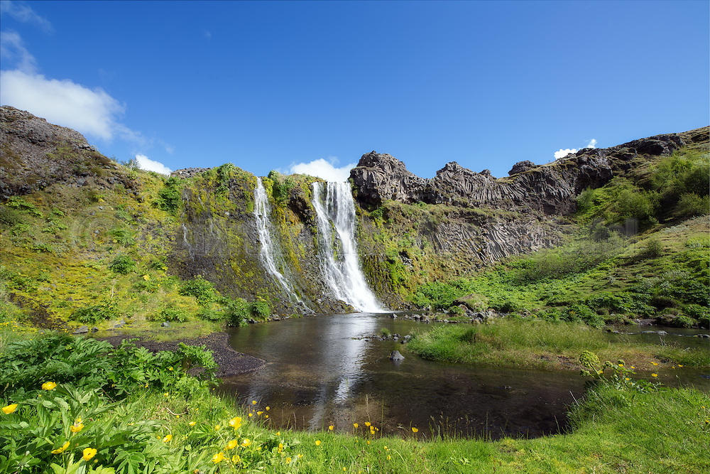 Waterfall in a green walley at Iceland, with a water in the front | En foss i en grønn dal på Island, med et vann i forgrunn.
