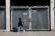Woman walks past heavily fortified gates on Kentish Town Road, London. Security includes locks, barred doors and anti climb rotating spikes.