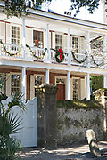 A historic home decorated with a Christmas wreath and roping on Church Street in Charleston, SC.