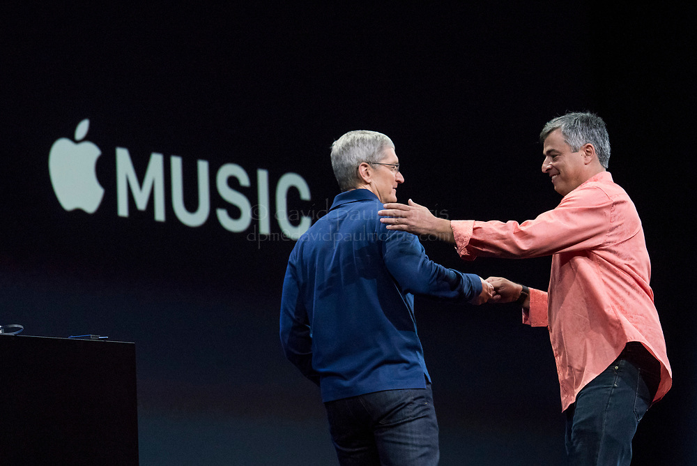 Eddy Cue, senior vice president of Internet Software and Services at Apple Inc., right greets Tim Cook, chief executive officer of Apple Inc., on stage during the Apple World Wide Developers Conference (WWDC) in San Francisco, California, U.S., on Monday, June 8, 2015. Apple Inc., the maker of iPhones and iPads, will introduce software improvements for its computer and mobile devices as well as reveal new updates, including the introduction of a revamped streaming music service. Photographer: David Paul Morris/Bloomberg *** Local Caption *** Eddy Cue
