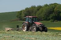 Das Wetter ist gut und ein Bauer arbeitet mit Traktor und Heuwender auf dem Feld, so dass das Gras besser trocknen kann. | The weather is good and a farmer is working on his tractor with hay turning machine