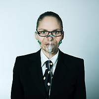 studio shot portrait of a beautiful young woman in a costume suit with oxygen mask