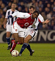 Photo. Jed Wee.<br /> West Bromwich Albion v Arsenal, Carling Cup, The Hawthorns, West Bromwich. 16/12/2003.<br /> Arsenal's Nwankwo Kanu (front) beats West Brom's Ronnie Wallwork.