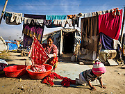 04 MARCH 2017 - KATHMANDU, NEPAL: A woman's son plays while she does her laundry in front of her tent in an IDP camp in the center of Kathmandu. The camp opened days after the April 2015 earthquake devastated Nepal, killing almost 9,000 people. At its peak, about 1,800 families lived in the camp. The camp is still open nearly two years after the earthquake, about 400 families currently live in the camp. Camp residents say the Kathmandu municipal government is trying to close the camp and is encouraging residents to find new housing. They said the government is cutting off services to the camp and last week stopped the free distribution of water, although water can be purchased for delivery. Most of the people in the camp came to Kathmandu from rural villages in the mountains in the weeks after the earthquake. Many of the residents of the camp, technically homeless, have found work in Kathmandu's bustling construction industry, rebuilding homes destroyed in the earthquake.       PHOTO BY JACK KURTZ