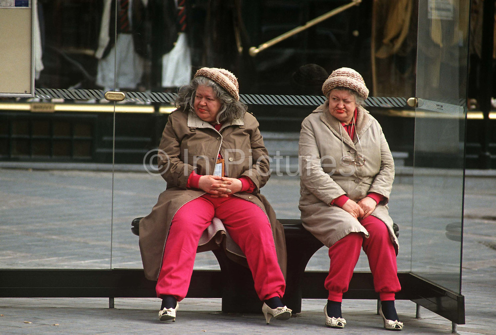 Identical and eccentric twin sisters wait for buses at a stop's shelter in central Brussels. Dressed almost identically too, with matching lipstick, shoes and sports trousers, the pair look towards oncoming traffic making sure they don't miss their bus home from central Brussels to a suburb. The eccentric pair has adopted the same posture in a way that twins and sisters sharing the same genetic characteristics and habits often do.